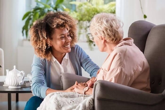 Oudere dame krijgt bezoek van een vrouwelijke zorgverlener.